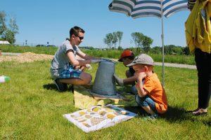 Dzieci oklejają kószkę gliną