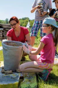 Dzieci i rodzice oklejają kószkę gliną